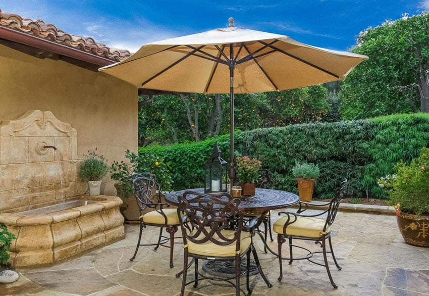 Outdoor patio with water fountain and small round table with umbrella