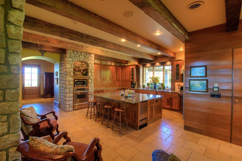 Rustic wood kitchen with exposed beams stone walls and tile flooring