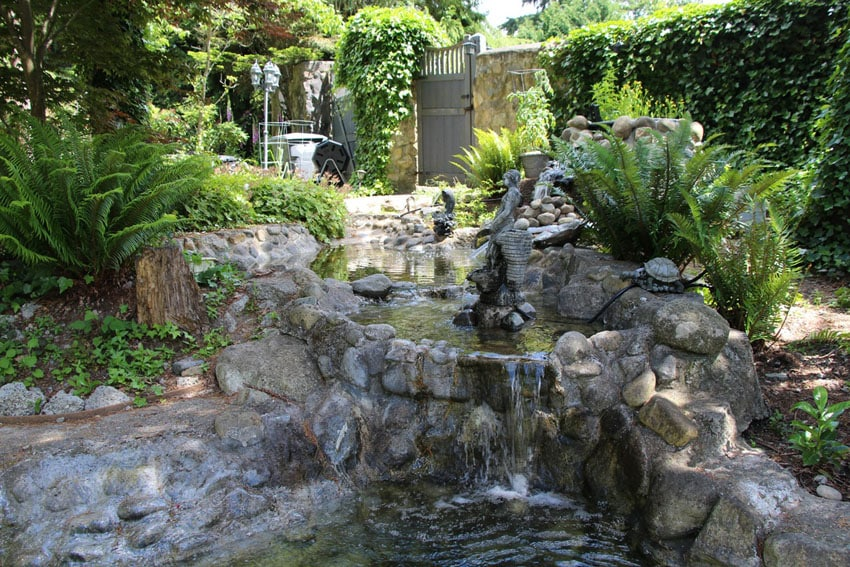 Garden landscaping with stone waterfall and pond