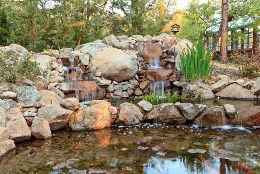 Rustic rock waterfall in backyard