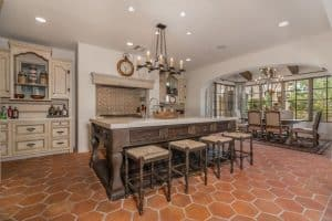 spanish-style-kitchen-with-off-white-base-cabinets-dark-island-terra-cotta-floors