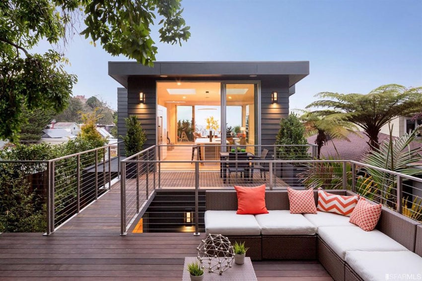 Contemporary wrap around deck with metal railings and l shaped couch