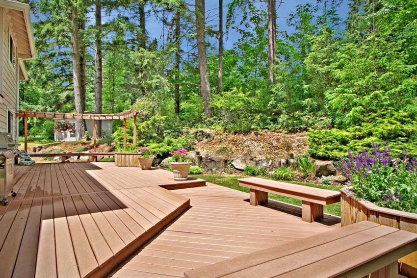 Deck with pergola and benches overlooking landscaped backyard garden