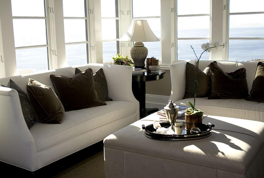 Ocean view living room with white sofas and brown pillows