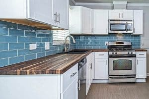 small-l-shaped-kitchen-with-white-cabinets-blue-subway-tile-and-wood-countertops
