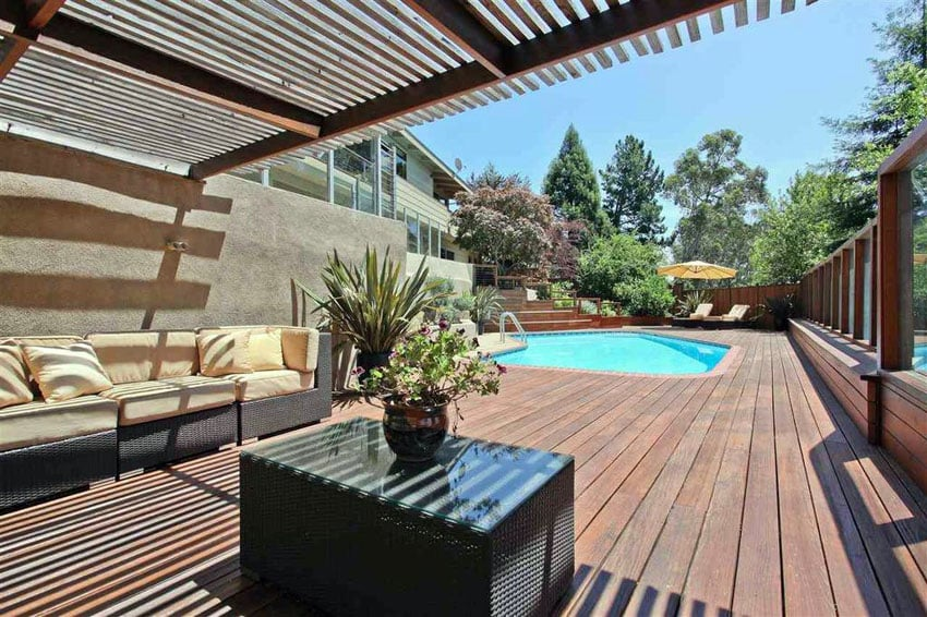 Wood deck surrounding swimming pool with pergola