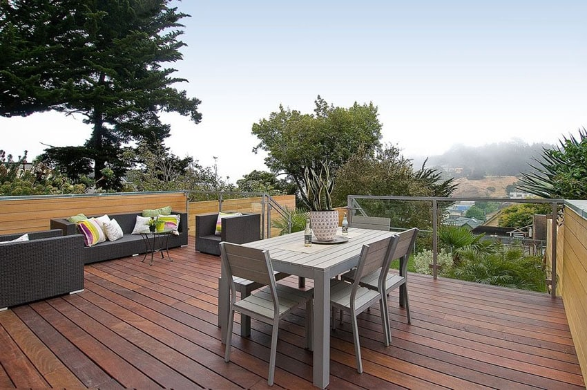 Wood deck with hillside views, synthetic chairs, sofa and outdoor dining table