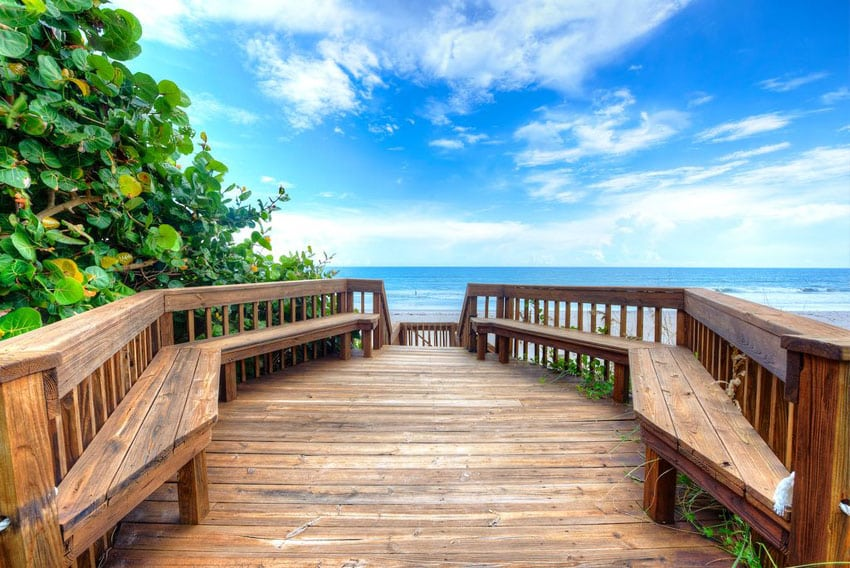 Wood deck with sitting benches leading to ocean