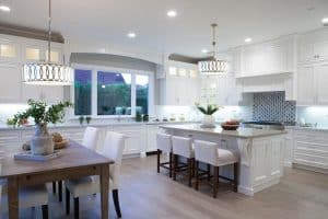 beautiful-contemporary-kitchen-with-white-cabinets-gray-granite-counter-dining-island-and-wood-flooring