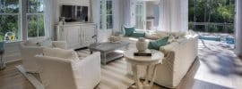 cottage-style-living-room-with-white-furniture-french-doors-and-window-views-to-backyard