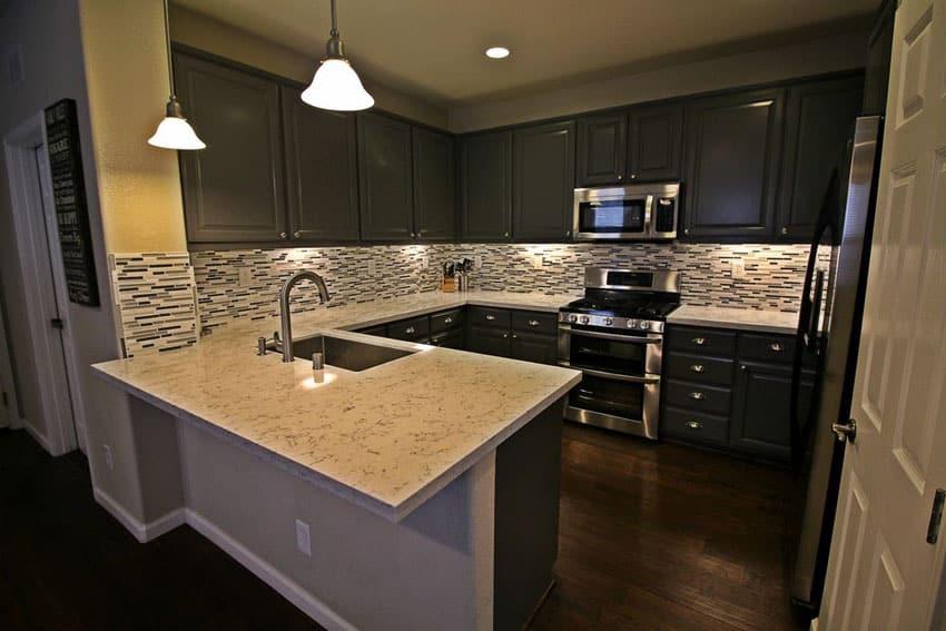 Dark cabinet kitchen with peninsula and mosaic tile backsplash
