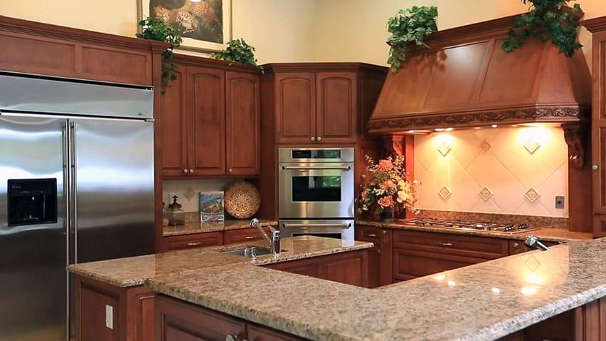 Luxury kitchen with custom exhaust hood and brown granite countertops
