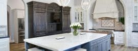 beautiful-country-kitchen-with-white-cabinets-hardwood-floors-gray-island-and-bianco-venatino-marble-surface