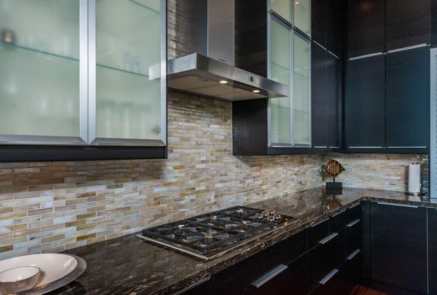 Black cabinet kitchen with glass fronts, granite counter, glass backsplash and five burner gas range