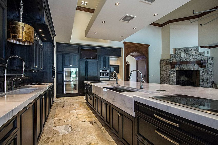 Contemporary black cabinet kitchen with carrara marble counters, gold drum pendant light and limestone flooring