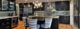 contemporary-kitchen-with-dark-cabinetry-porcelain-tile-backsplash-light-wood-floors-and-tear-drop-pendant-lights