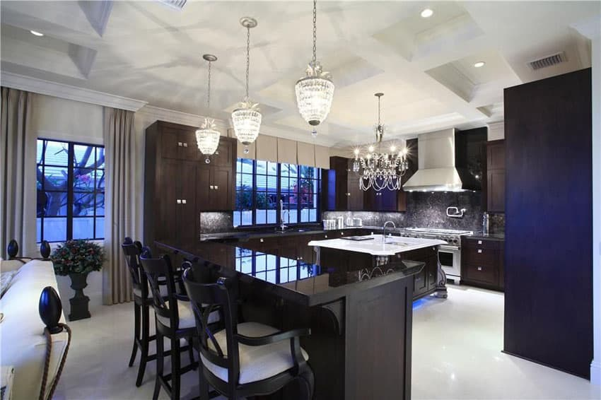 Dark cabinet modern kitchen with 12 light chandelier, black granite counters and white carrara marble island