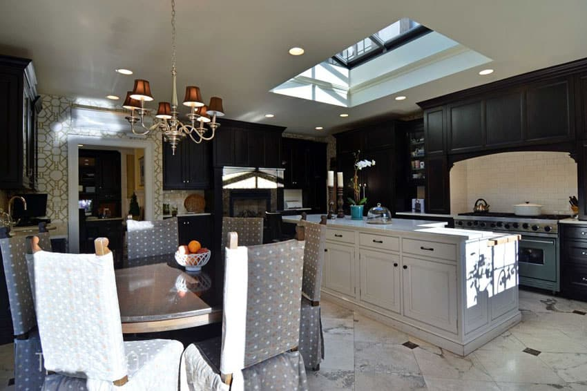 Dark wood cabinet kitchen with white island and skylight