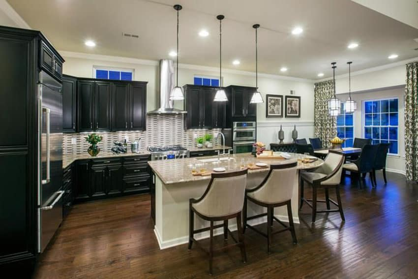 Kitchen with black cabinets, light color granite island and l shape design with open layout