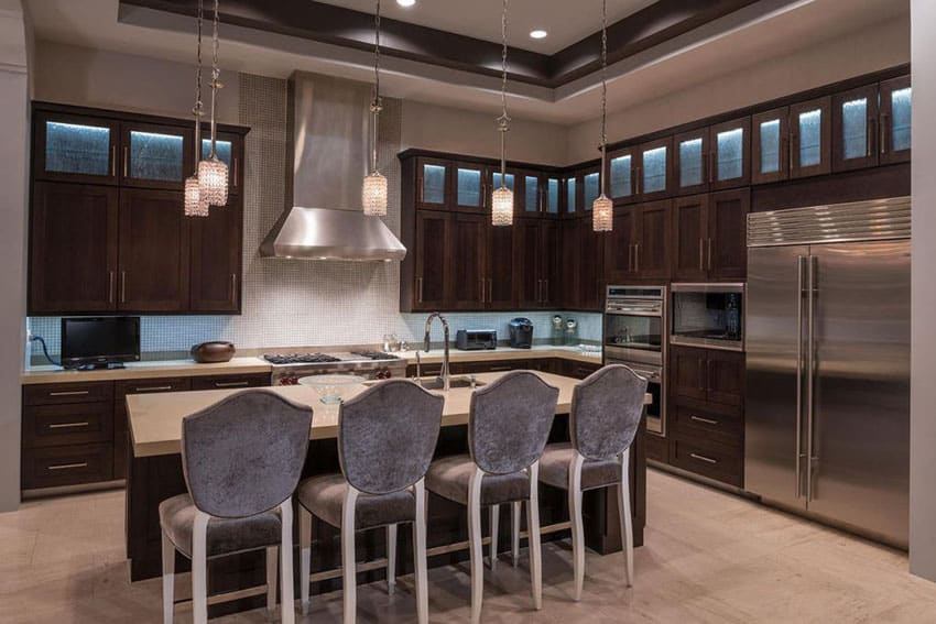 Kitchen with dark wood cabinets, breakfast bar island and italian cream marble counters