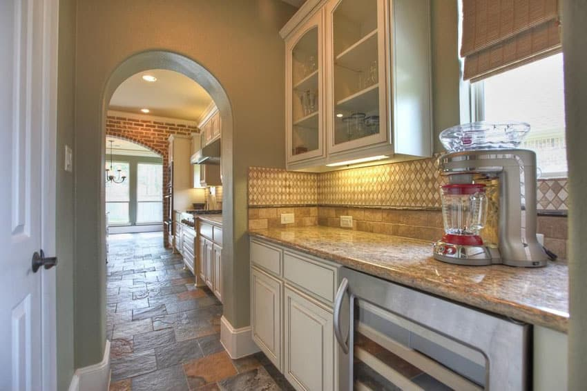 Traditional single wall kitchen with glass door, white cabinets and stone floors