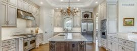 luxury-kitchen-with-antique-white-cabinets-carrara-marble-counter-island-and-walnut-floors