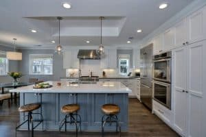 luxury-kitchen-with-white-shaker-cabinets-blue-island-with-white-marble-counters-and-globe-pendant-lights