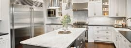 luxury-white-cabinet-kitchen-with-gray-island-black-counter-and-wood-floors