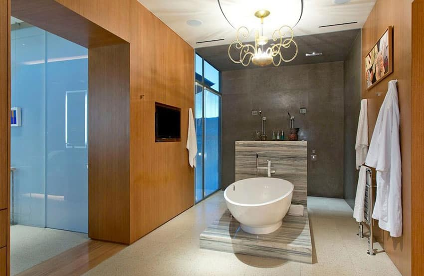 Modern bathroom with elevated freestanding tub and gold chandelier