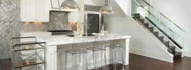 modern-kitchen-with-white-cabinets-metal-backsplash-engineered-hardwood-floors-and-chrome-pendant-lights
