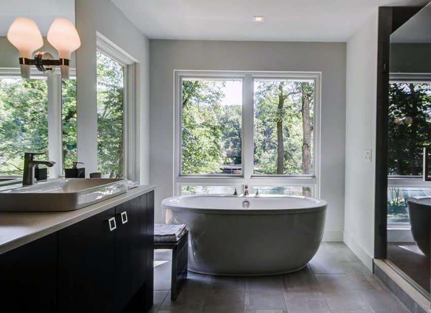 Modern master bathroom with bathtub window views, dark vanity and porcelain tile floors