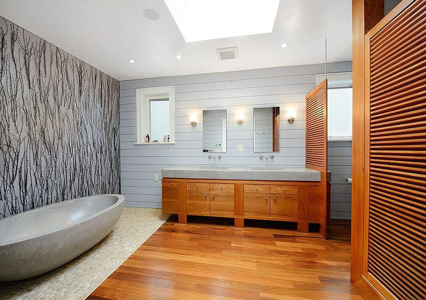 Modern master bathroom with custom travertine bathtub and natural river rock floor