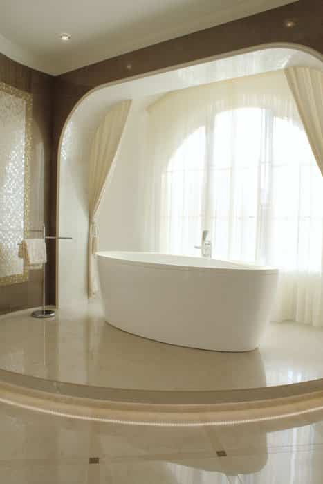 Modern minimalist bathroom with bathtub on elevated patform and large window