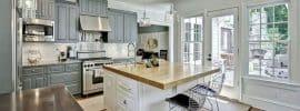 traditional-kitchen-with-gray-cabinets-white-island-white-subway-tile-and-wood-countertops