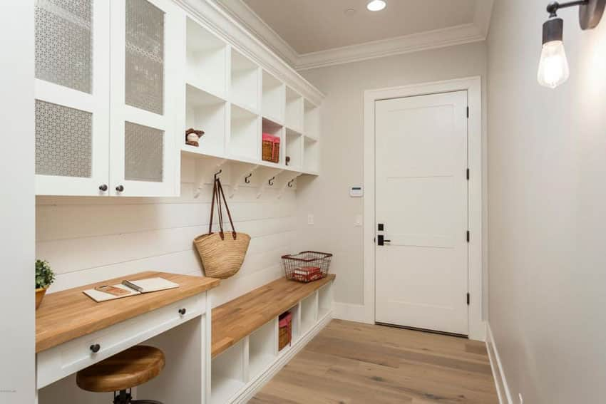 Contemporary mud room with white cabinets with cubbies and wood bench