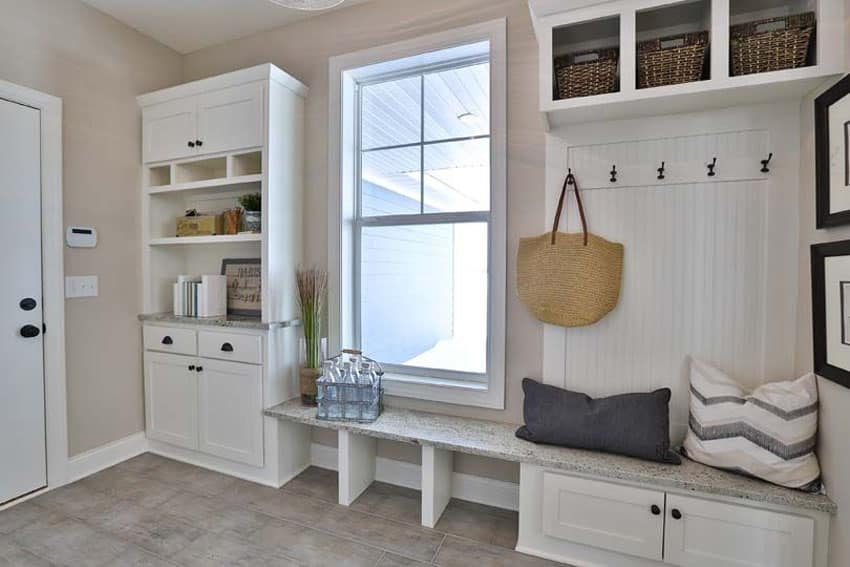 Cottage style mud room with white cabinets and bench seating