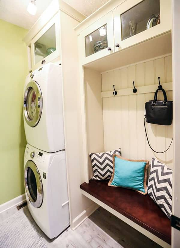 Cozy mudroom bench with clothing hangers next to laundry