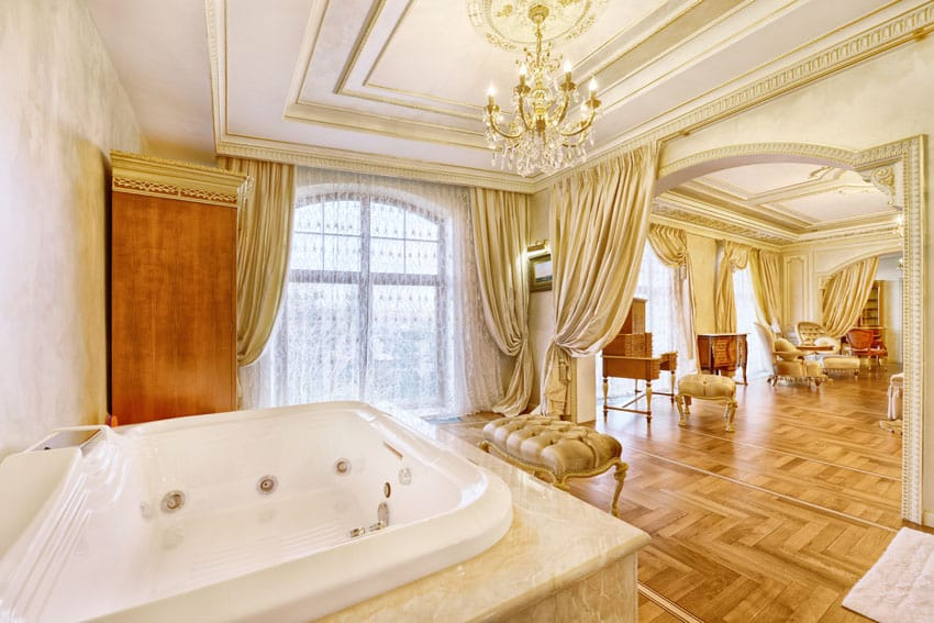 Bathroom with gold decor, chandelier, wood flooring and whirlpool tub