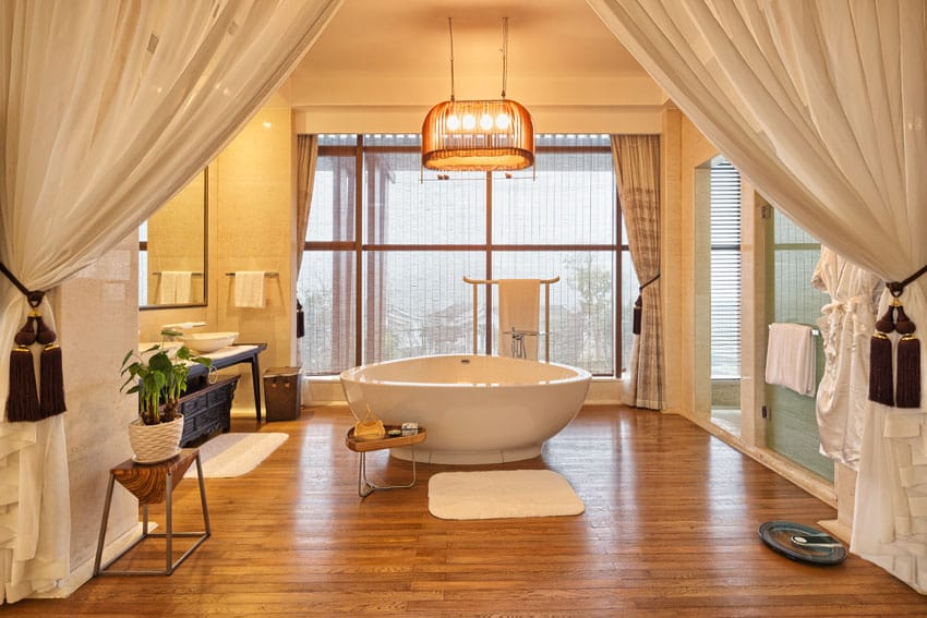 Master bathroom with large curtains, wood floors and freestanding tub
