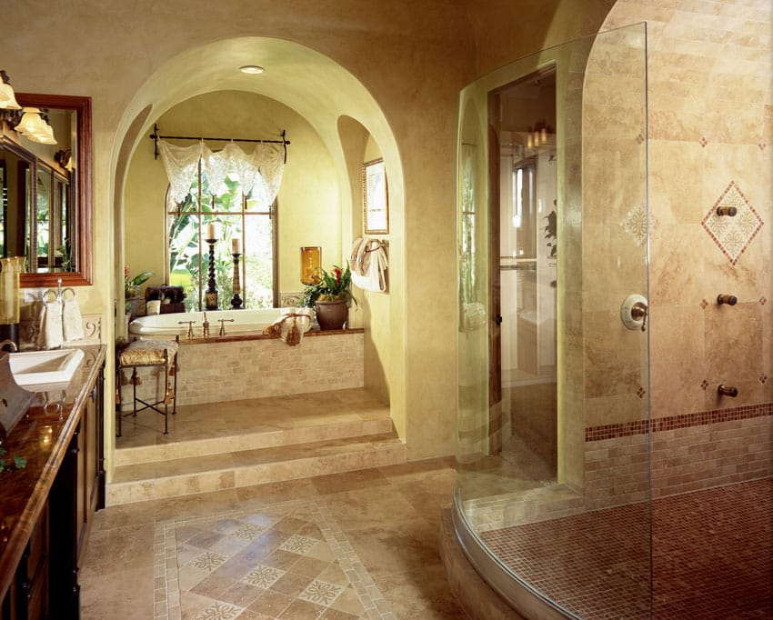Mediterranean style tile bathroom with brown color theme and arched doorway to tub