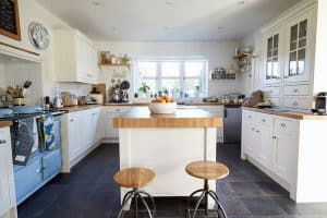 white-cabinet-kitchen-with-light-wood-counters-and-vintage-blue-oven
