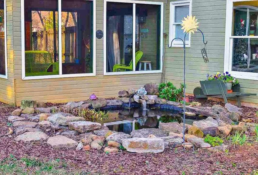 Backyard pond with wheelbarrow flower planter