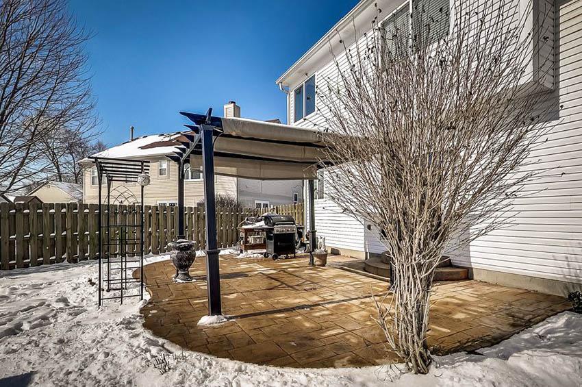 Backyard pergola with retractable shade canopy