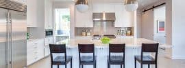 kitchen-with-white-cabinets-and-light-color-laminate-floors-and-long-breakfast-bar-island-with-marble-countertops