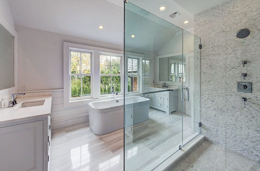 Master bathroom with large clear glass, shower door with white mosaic tile and dual vanities