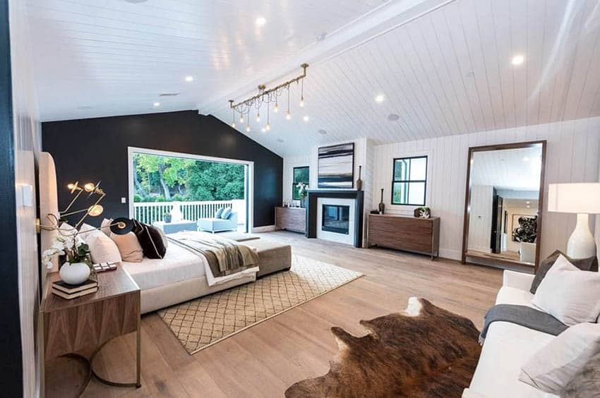 Modern masculine bedroom design with black accent wall linear pendant lighting wood floors and animal hide