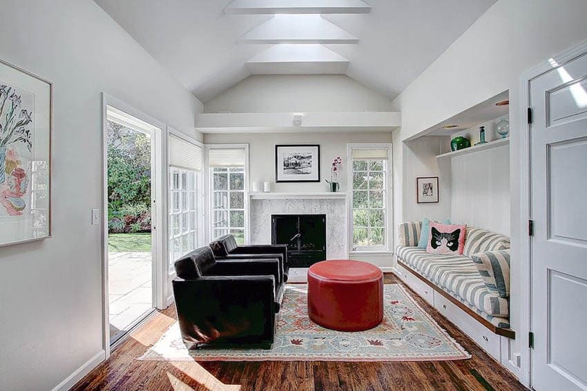 Living room with built in seat and wood floors with picture windows