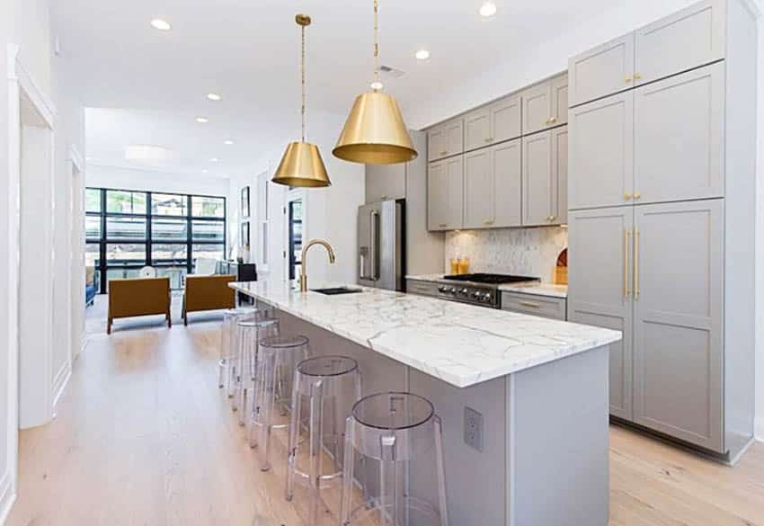Contemporary kitchen with gray cabinets, gold hardware and marble countertops island