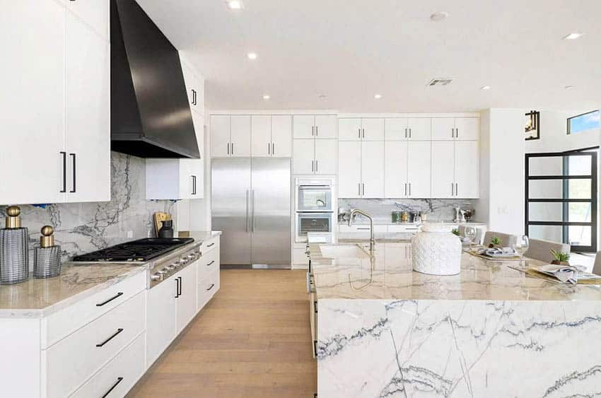 Contemporary kitchen with white cabinets, black oven hood and waterfall quartz countertop island