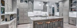 contemporary-kitchen-with-light-gray-cabinets-light-wood-floors-and-white-textured-backsplash